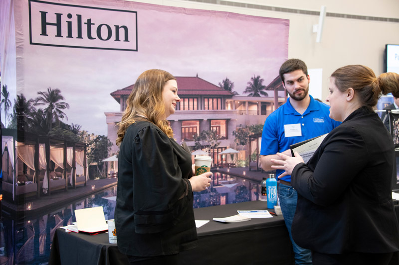 Student speaking with Hilton group members